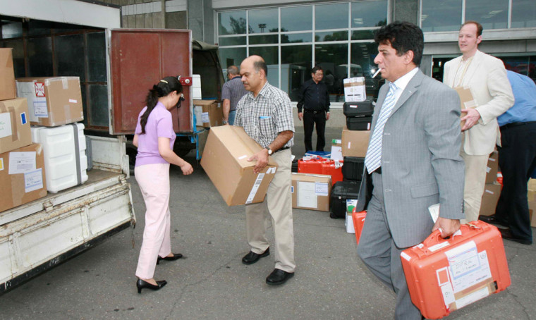 In this photo released by China's official Xinhua news agency, Adel Tolba, front right, head of the International Atomic Energy Agency's inspection team, loads equipments onto a truck with his team members, upon their arrival in Pyongyang, North Korea, on Saturday.