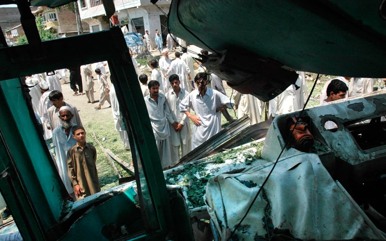 Local residents are seen through the damaged window of a bus at the site of a suicide bombing in Matta