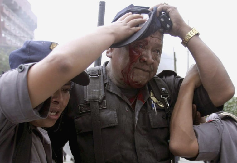 An injured policeman is helped by his colleagues after clashes with demonstrators near the colonial city centre of Oaxaca