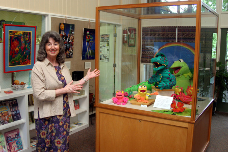 Emily Kearney, hostess at the Jim Henson Delta Boyhood Exhibit in Leland, Miss., stands next to an exhibit of Henson's early puppets.