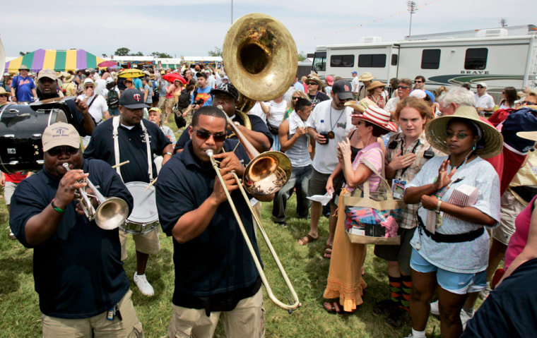 """A traditional Jazz band winds its way through the crowd at the New Orleans Jazz and Heritage Festival in New Orleans. A trip to see traditional jazz in New Orleans would make for a nice summer vacation, but could also could be considered """"geotourism""""."""