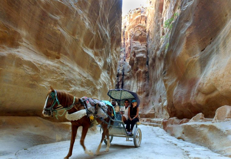 FOREIGN TOURISTS RIDE THROUGH ANCIENT CITY OF PETRA IN JORDAN