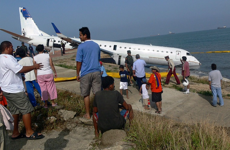 People look at an Embraer 190 aircraft that performed an emergency landing yesterday at Simon Bolivar airport in Santa Marta