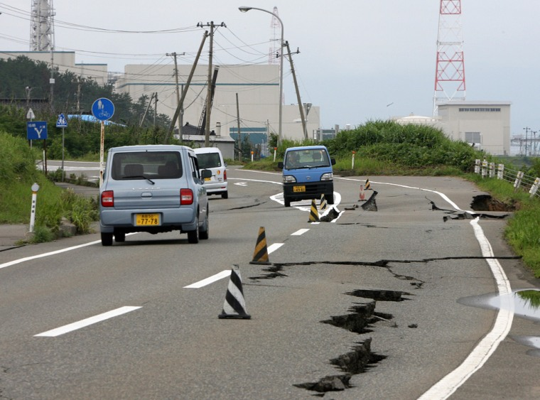 Vehicles drive on a damaged road leading