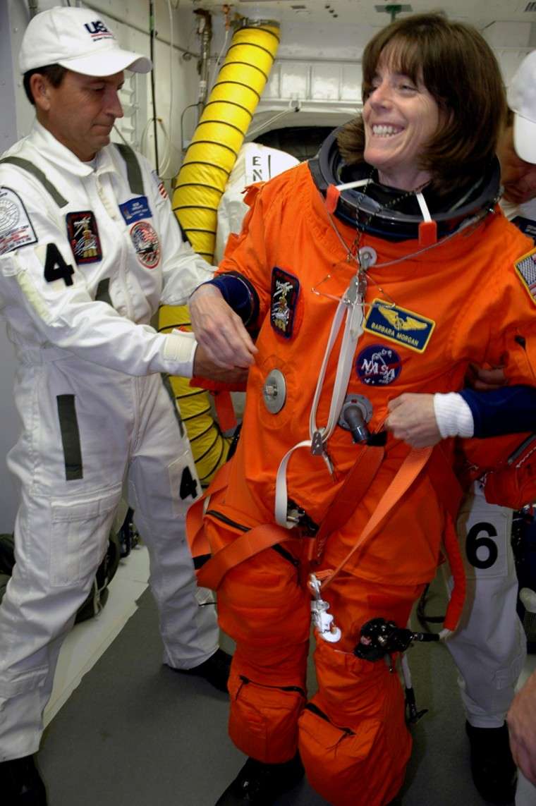 Workers help teacher-turned-astronaut Barbara Morgan get ready to enter the shuttle Endeavour's cabinfrom the White Room at Launch Pad 39A during a countdown rehearsal on Thursday.