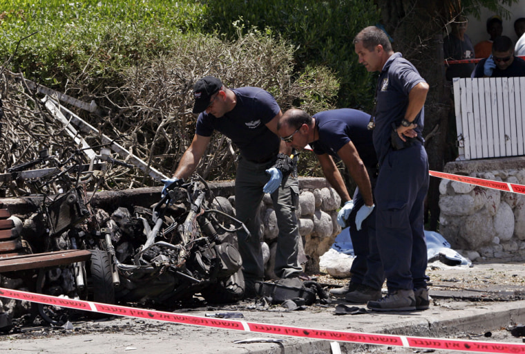 Israeli police officers examine a motorcycle that exploded, killing Arik Korkus, 33, a criminal and a former elite infantry soldier, in the town of Ashkelon on June 27. Israel's rival underworld gangs have been waging a bloody battle for years over gambling operations and other lucrative businesses, targeting each other with bullets, bombs and anti-tank missiles.