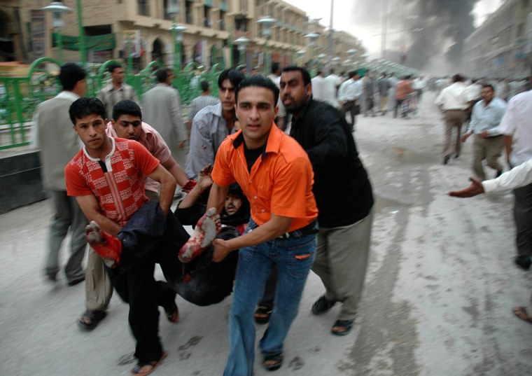 Residents carry a wounded victim away from the scene of a suicide car bomb attack in Kerbala