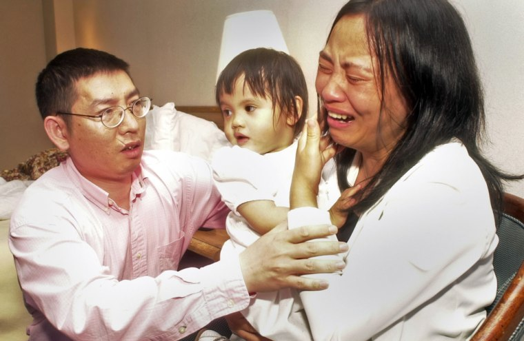 Shaoqiang He, left, comforts his wife, Qin Luo He, as she holds their daughter, Avita He, in their hotel room in Memphis, Tenn., on May 12, 2004. Avita He, now named Anna Mae He, has been returned to her parents' custody.