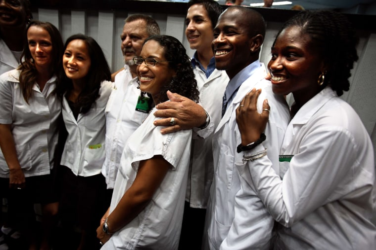 U.S. medical students, attending their graduation ceremony from Cuba's Latin American School of Medicine, pose Tuesday at the Karl Marx Theatre in Havana. From left to right, they are Melissa Barber, upper left corner, Carmen Landau, Wing Wu , unnamed professor, Evelyn Erick, Jose De Leon, Tussaint Reynolds and Teresa Thomas.