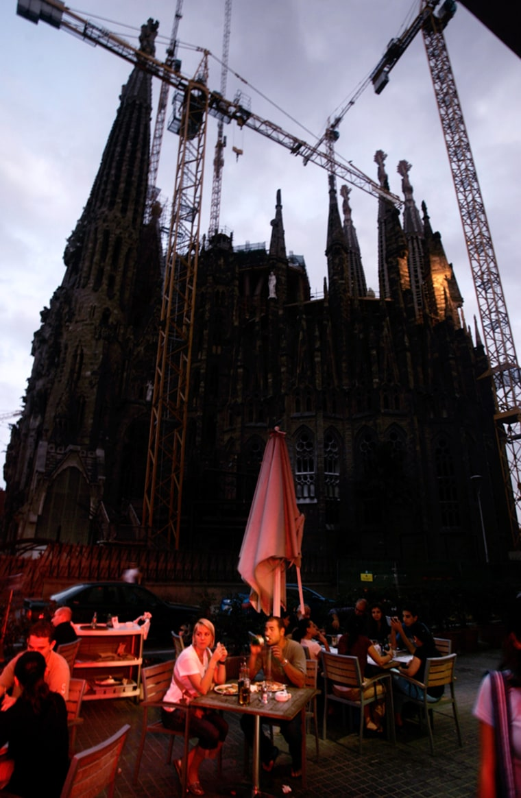 Tourists have dinner Tuesday in front of the Sagrada Familia cathedral, seen without its usual illuminations in Barcelona.