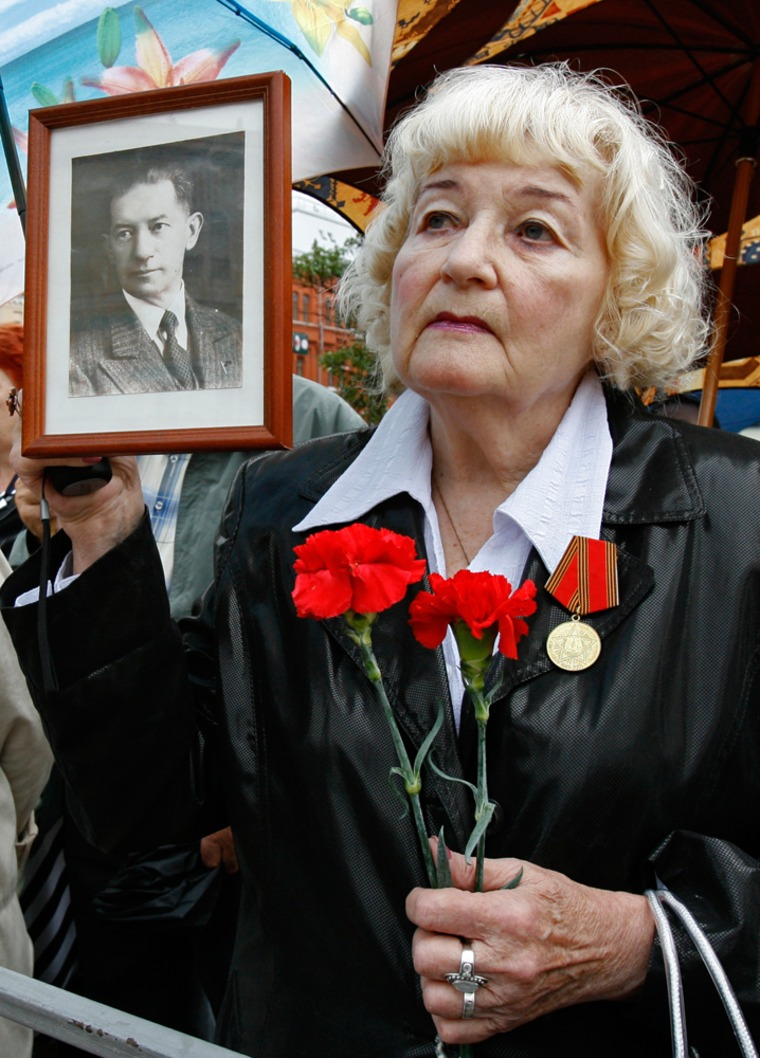 Irina Kalina, 79, holds a portrait of herfather, Ignaty, who wasaccused of being a spy and died in jail.Irina was sent to a labor camp in Kazakhstan for five years.