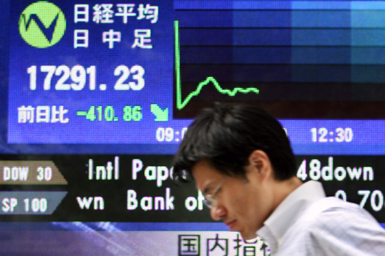 A man walks past a share prices board in