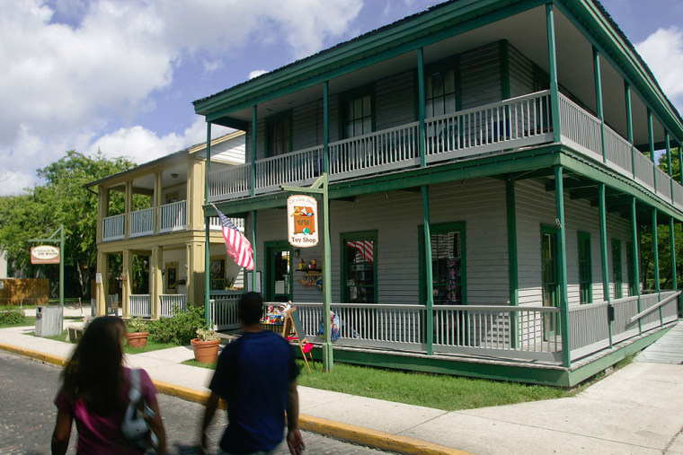Tourists walk past The Cuna Street Toy Shop, right, and Knock on Wood, two historic buildings on Cuna Street in the historic section of St. Augustine, Fla. The two shops are housed in two of dozens of historic buildings the University of Florida will be maintaining for the City of St. Augustine, Fla. The maintenance and upkeep of the building has become too expensive for the nation's oldest city.