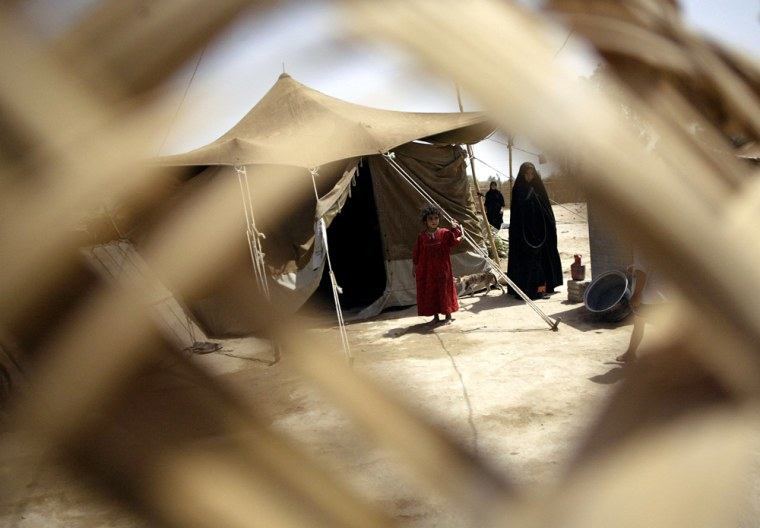 A family stands outside their tent at the refugee camp they have called home for the last year in the Shiite holy city of Najaf, south of Baghdad, Iraq, on Monday