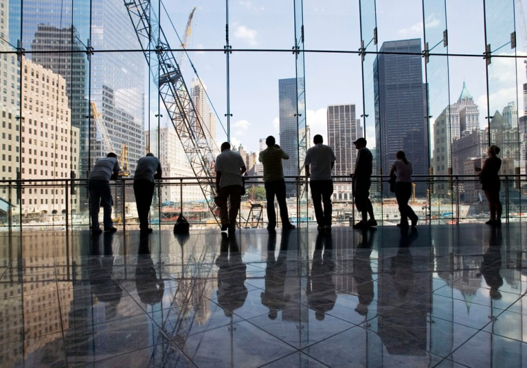 Visitors to the World Trade Center take in a view of the construction at ground zero on Wednesday in New York.