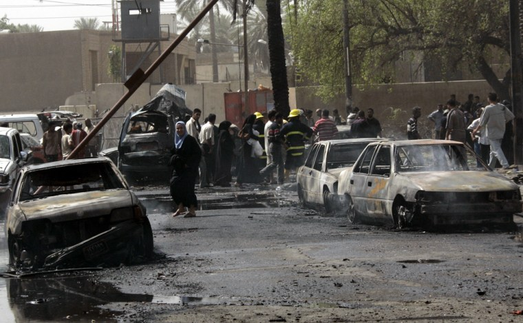 Iraqis mill around the site where a parked car bomb killed 17 civilians and wounded dozens more on Wednesday in Baghdad.