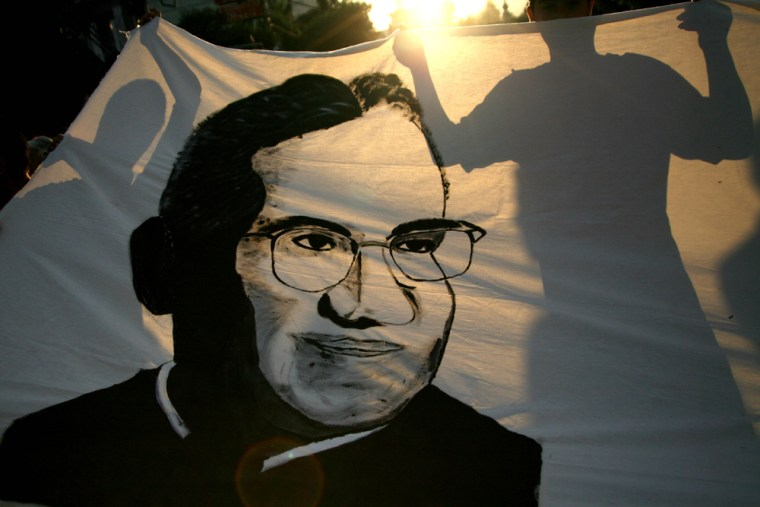 Demonstrators are silhouetted on a banner with the image of slain Archbishop Oscar Arnulfo Romero in San Salvador, El Salvador, on March 24. Romero, who was assassinated while celebrating Mass on March 24, 1980.