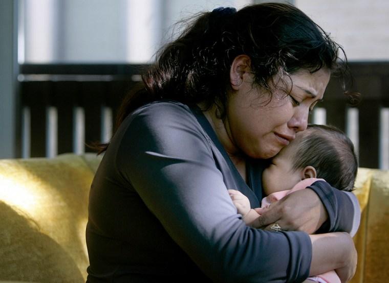 Abundia Martinez weeps as she hugs her 2-month-old daughter, Lorena Trinidad Martinez, at their home in Minneapolis. Abundia's husband, Artemio, was killed in Wednesday's bridge collapse.