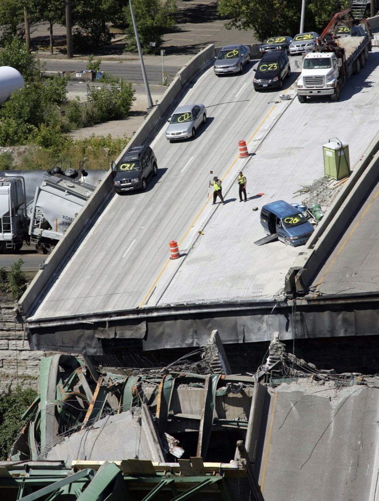 Emergency personnel survey the remains of the I-35W bridge in Minneapolis