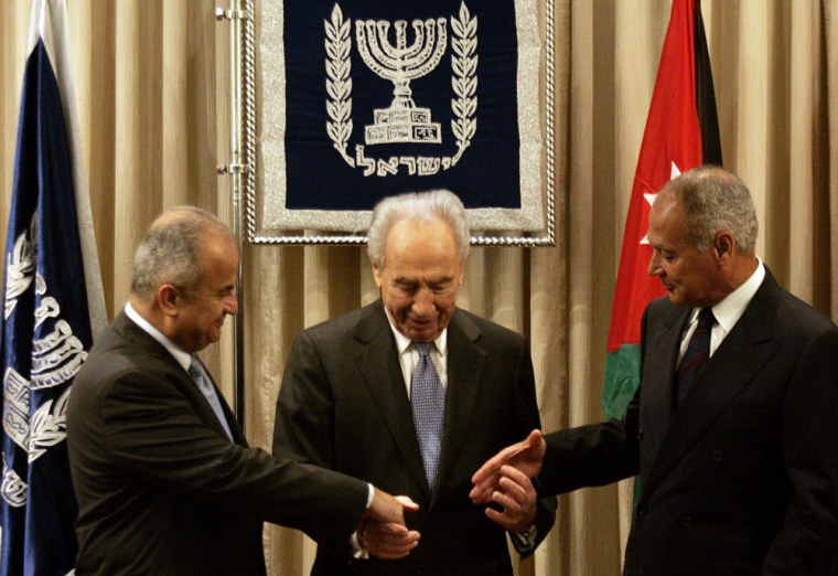 Israel's President Shimon Peres, center, joins hands with Egyptian Foreign Minister Ahmed Aboul Gheit, right, and Jordan's Foreign Minister Abdul-Ilah Khatib, left, duringtheir historic visit to Israel.
