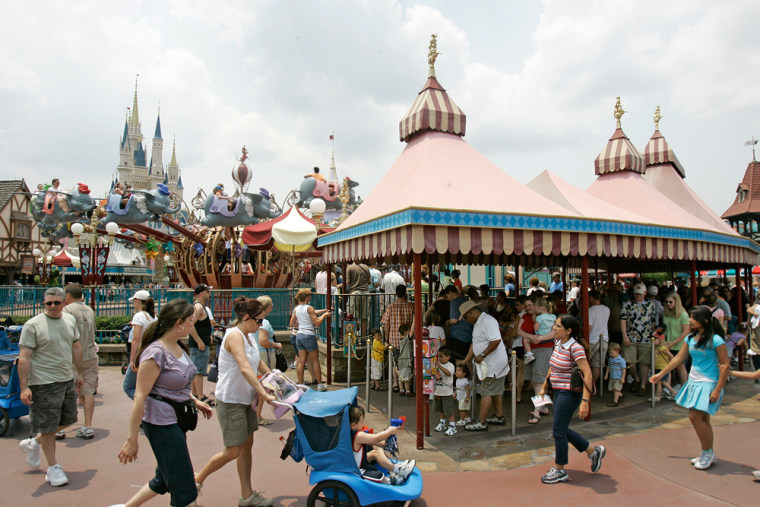 Guests wait in long lines for the Dumbo ride at the Walt Disney World Magic Kingdom theme park in Lake Buena Vista, Fla., earlier this year.