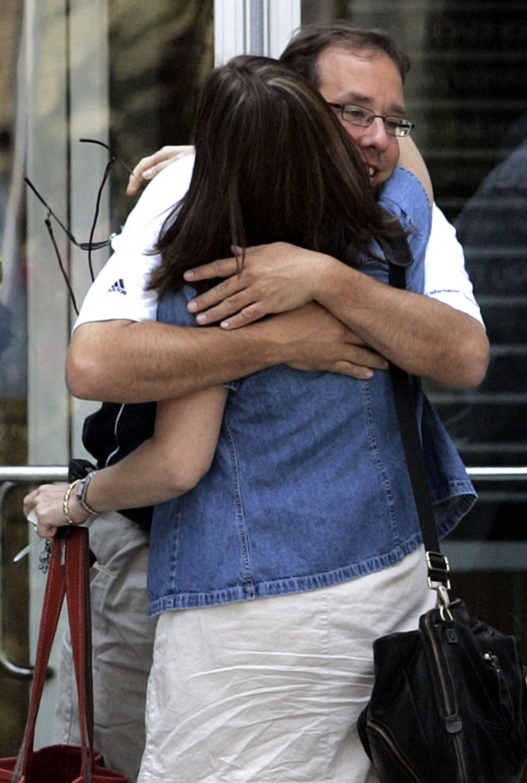 Employees hug each other as they leave the building of American Home Mortgage Investment Corp. in Melville, New York.