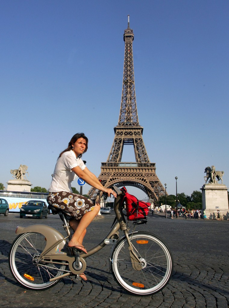 A rider uses a new bicycle provided by Paris City Hall, around the Eiffel Tower in Paris. More than 10,600 bikes are posted at 750 stations all over the city and prices start at a euro (U.S. $1.36) for a one-day pass. Users can take a bike and put it back at any station around town.