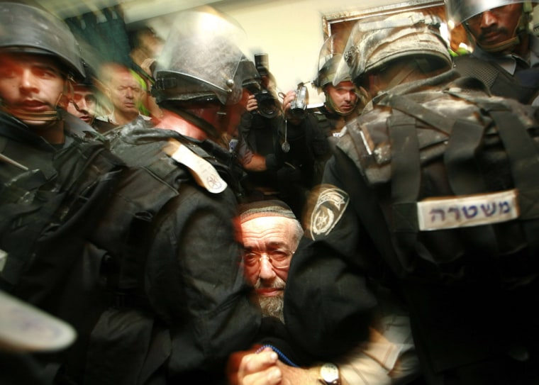 Israeli security forces restrain a settler in the West Bank city of Hebron