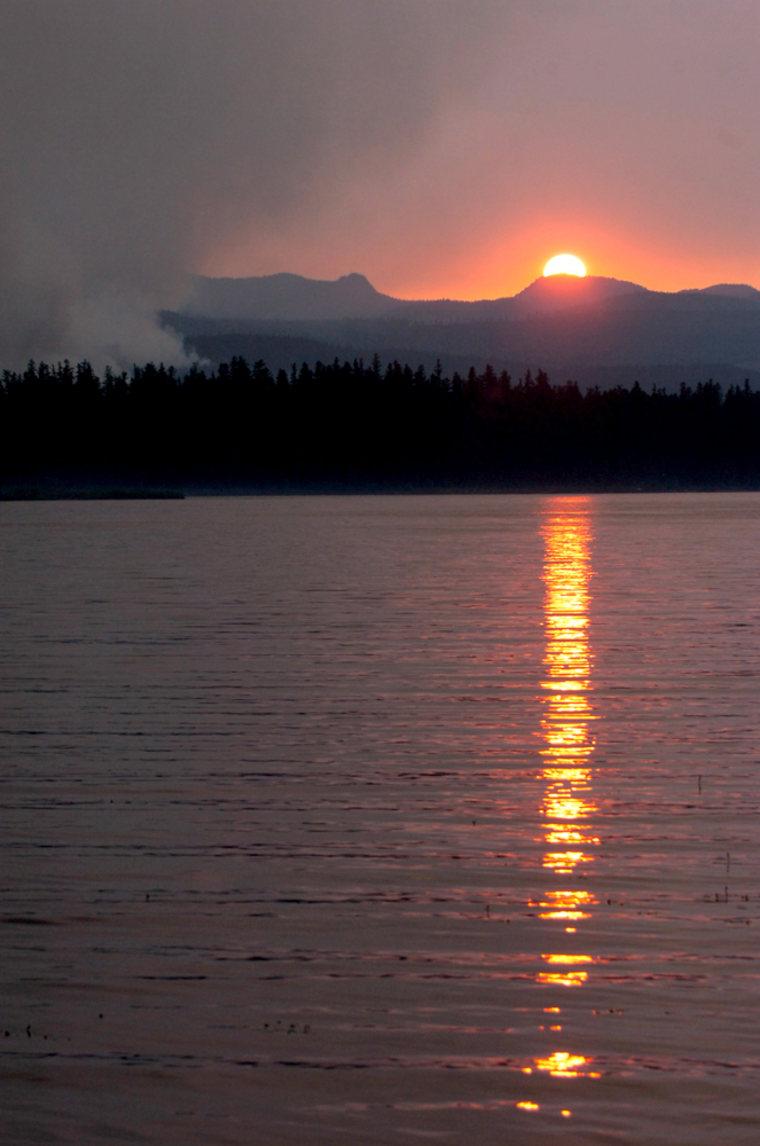 The sun sets Mondayas the Jacko Lake fire burns near Seeley Lake in Montana.