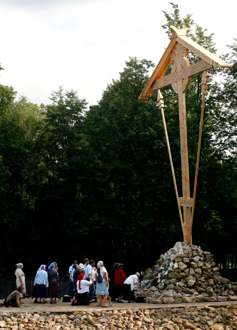 Hundreds of people laid flowers and lit candles under the 40-foot woodencross Wednesday.