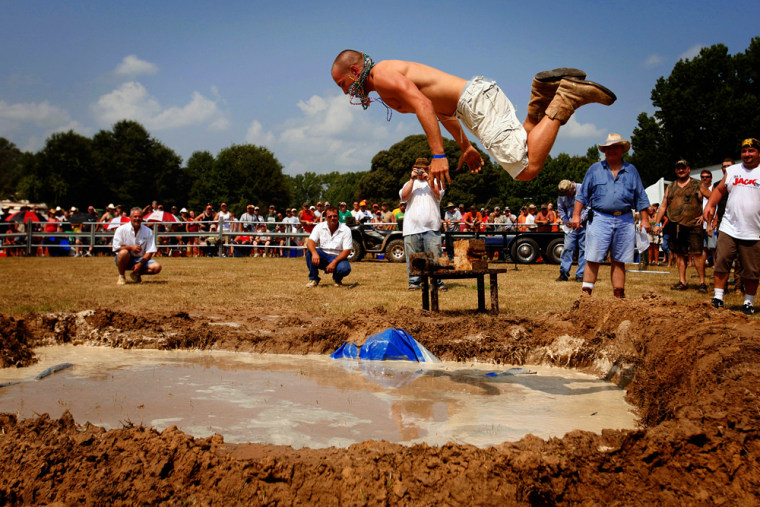 Blake Harris belly flops into the mud pit during the Texas Redneck Games at the Pool Ranch in Athens, Texas, last week. For three days, hordes of legit and wannabe rednecks convene to drink, race their ATVs, and compete in events such as spam eating and mattress throwing.