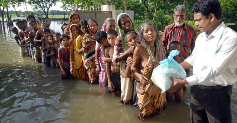 A flood relief officer distributes material outside a relief center in Bangladesh.