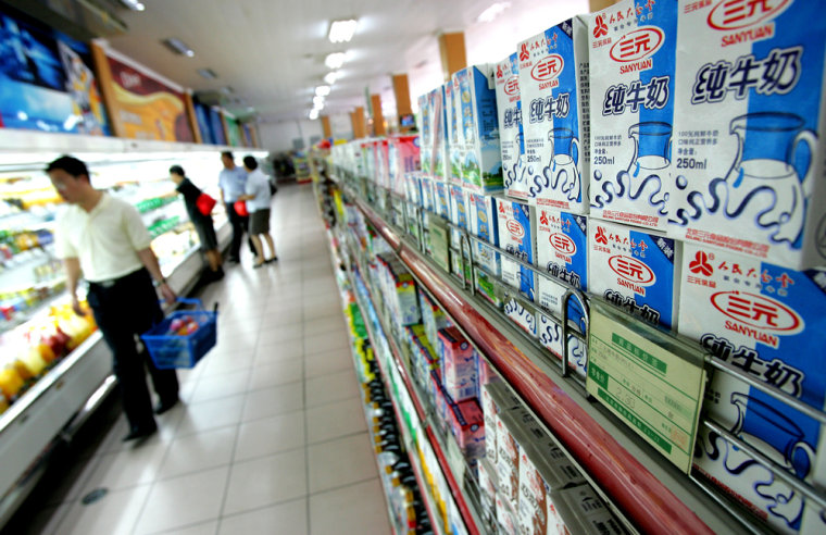 Customers walk past milk products at a supermarket in Beijing on Friday.