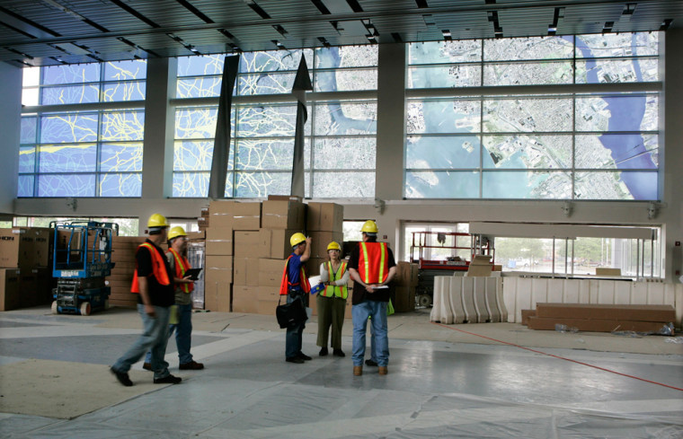 Contractors walk through the main lobby of the reconstructed Liberty Science Center in Jersey City, N.J. The translucent panels overhead depict a satellite view of the area around the science center on the right and the flow of data through human nerve cells on left.