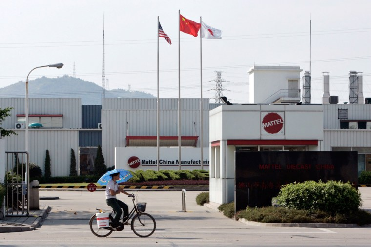 A woman cycles past the entrance to the Mattel factory in China's southern city of Foshan
