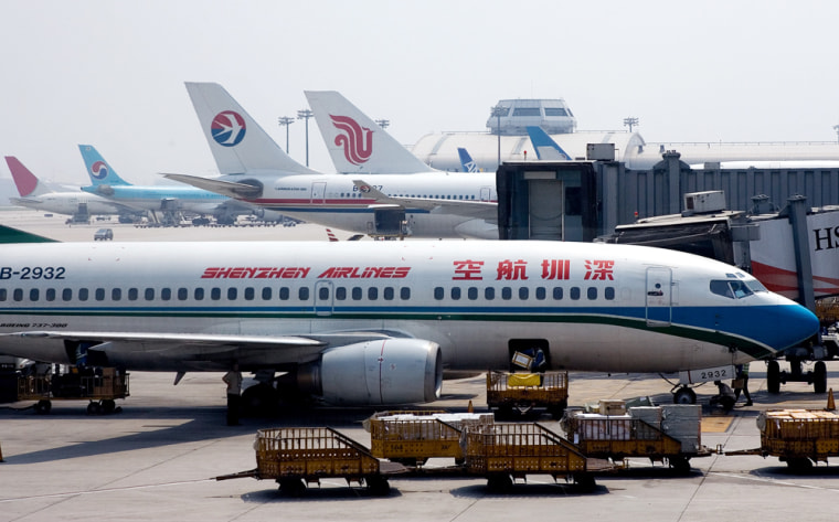 An airport worker unloads passenger luggage from a Shenzhen Airliner parked at the Beijing International Aiport. China's aviation authority, citing safety concerns, has announced plans to scale back flights at overstretched Beijing airport and a ban on the founding of new airlines before 2010.