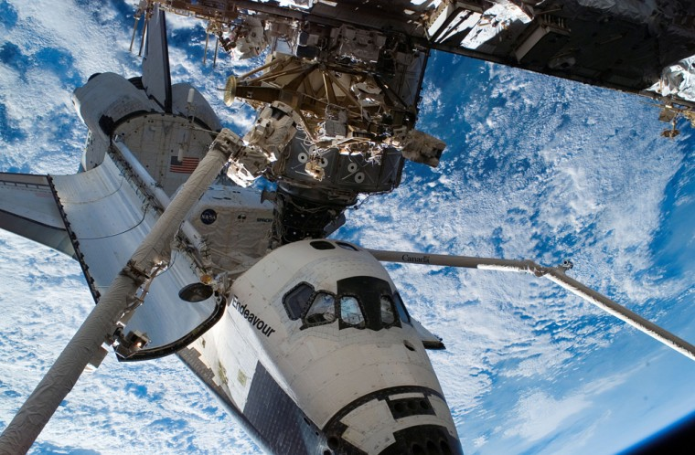 Earth serves as a backdrop for the space shuttle Endeavour as it is docked to the international space station's Destiny laboratory on Wednesday. Two robotic arms, attached to the station and to the shuttle, are visible in this image, taken from the station.