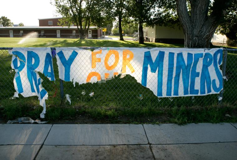 A tattered sign showssupport forsix miners missinginside a Utah mine.