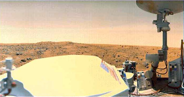 A Viking 1 Lander image of Mars' Chryse Planitia. The large white object at lower left and center, with the American flag on the side, is the spacecraft's radiothermal generator (RTG) cover.
