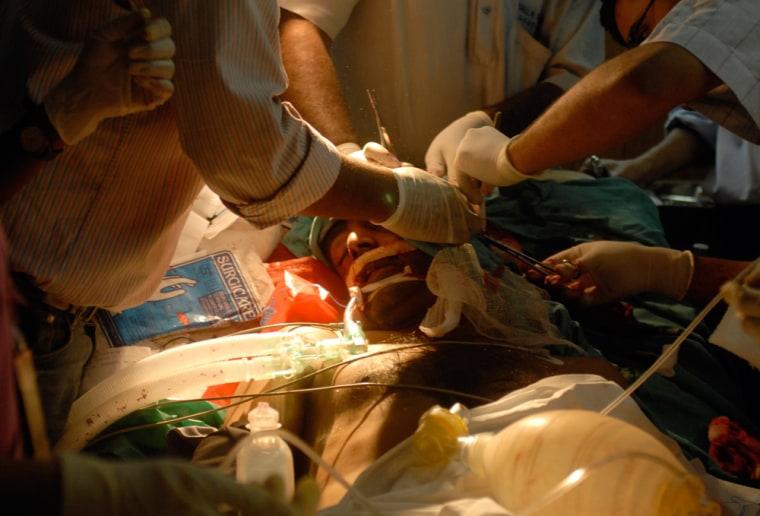 Medics treat a person injured in a bomb blast at a hospital near Lumbini Park