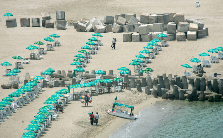 Large concrete blocks used in the construction of sea defenses intermingle with the umbrellas and beach chairs of tourists on the beach in Alexandria, Egypt, onMay 15. The Mediterranean Sea is creeping higher, flooding parts of the Egyptian shoreline.