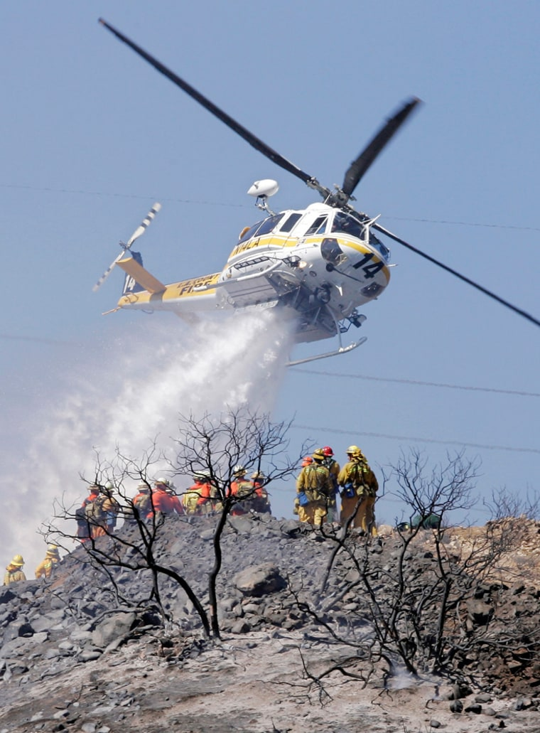 A Los Angeles County fire helicopter drops water on a brush fire as firefighters look on in the Sun Valley area of Los Angeles in July. Wildfires across the U.S. have scorched nearly 7 million acres of land this year, leaving exposed soil that's susceptible to erosion and mudslides. But entrepreneur Mike Krysiak believes he can help soil and vegetation recover faster using a simple solution that combines recycled-paper mulch and an organic powder.
