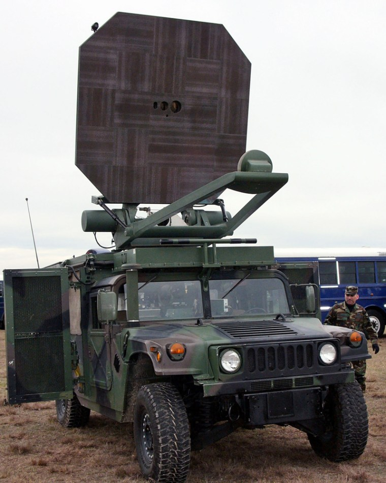 An unidentified airman looks over the military's Active Denial System, a non-lethal ray gun that was demonstrated at Moody Air Force Base, Ga. The system shoots a beam of energy that makes people feel they are about to catch fire.