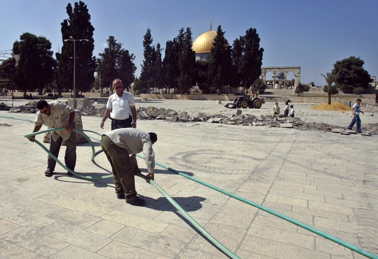 Workers lay pipes by a trench next to the Dome of the Rock, background, as part of construction carried out by Islamic authorities inside the Al-Aqsa mosque compound, in Jerusalem's Old City, on Thursday.