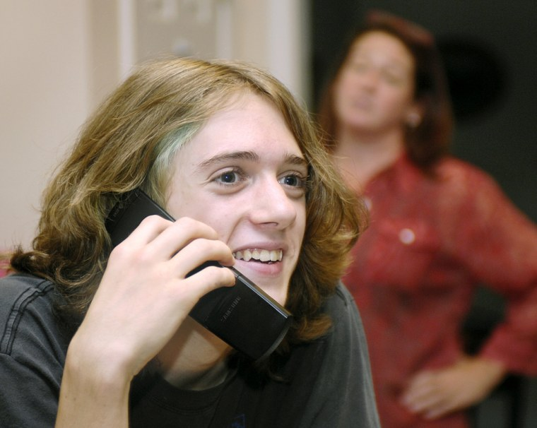 Sam Hill, 13, an eighth grader, speaks on a cell phone as his mother Carlton Hill, looks on in their Atlanta home. The Hill's have been using parental controls for the past four months on their cell phones. AT&T Inc., the United States' largest wireless carrier, will launch a service Tuesday giving parents wide-ranging control on almost all of its 63.7 million subscriber lines.