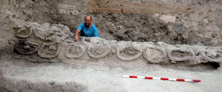 An archaeologist indicatesthe opening of one of the ancient beehives found in excavations in Rehov in Israel.