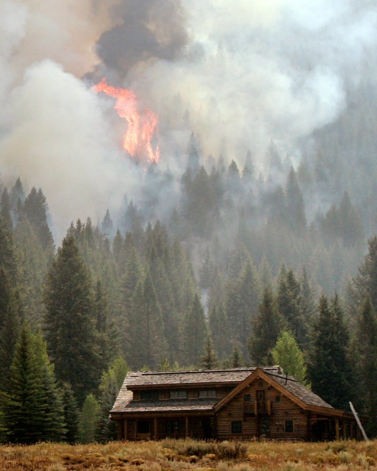 Flames and smoke roll above a home in the Warm Springs area of Ketchum, Idaho,on Aug. 30. When wildfires advanced on this wealthy vacation community, some people clambered aboard private jets and departed for clearer skies.