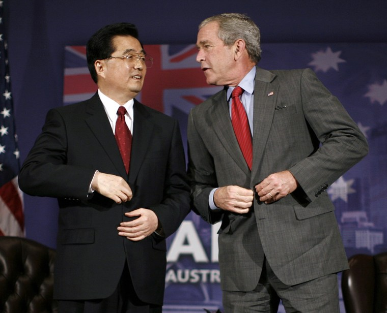 U.S. President W. Bush and Chinese President Hu adjust their jackets following their bilateral meeting in Sydney