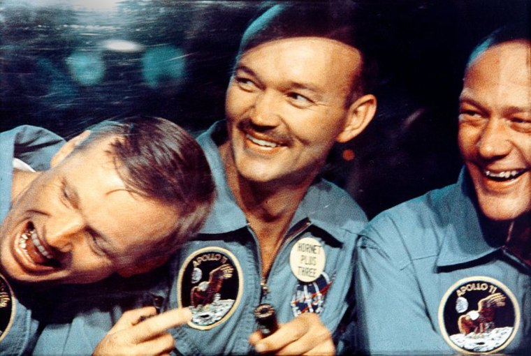 Apollo 11 astronauts Neil Armstrong, Mike Collins and Buzz Aldrin joke around as they peer out the window of an isolation chamber. The three were kept in quarantine for two and a half weeks after their flight.