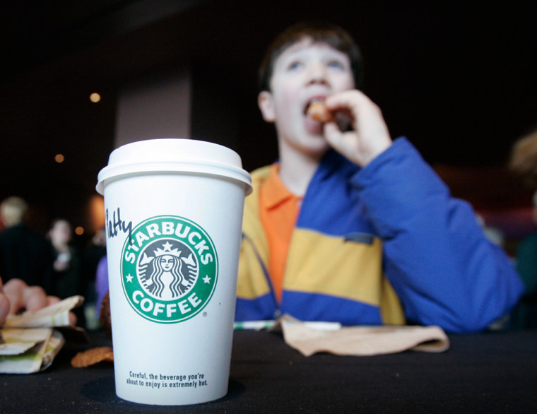 Dustin Doty, 13, enjoys apastry with his beverage atthe Starbucks annualshareholders meeting this year.Doty's mother recently purchasedshares of Starbucks stock for him.